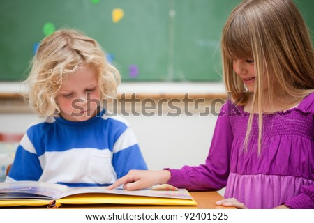Pupils reading a book in a classroom - stock photo