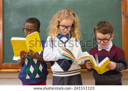 Pupils reading books at elementary school - stock photo