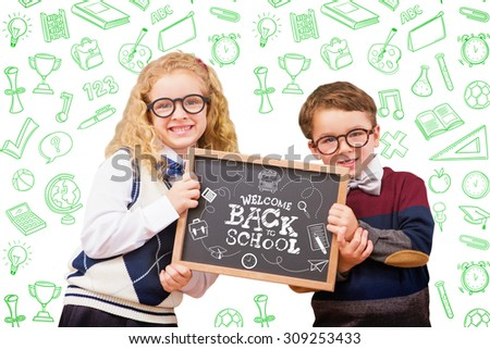 Pupils showing chalkboard against back to school - stock photo