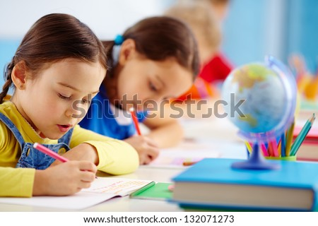 Pupils sitting in a row writing a test - stock photo