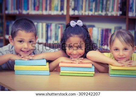 Pupils smiling at camera in library at the elementary school - stock photo