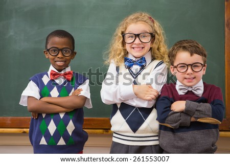 Pupils smiling at camera with arms crossed at elementary school - stock photo