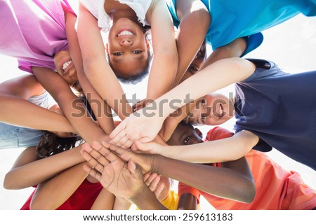 Pupils standing in a circle on a sunny day - stock photo