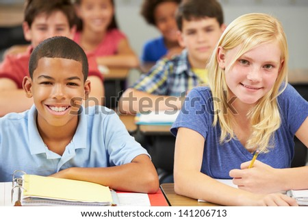 Pupils Studying At Desks In Classroom - stock photo