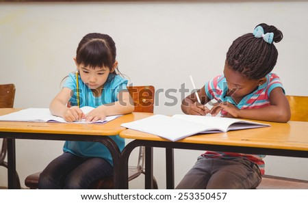 Pupils writing in notepad at their desk at the elementary school - stock photo