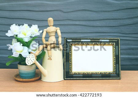 puppet doll and vintage frame with wooden wall background - stock photo