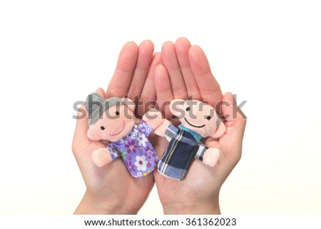 Puppet of the old couple in the hand/nursing care  - stock photo