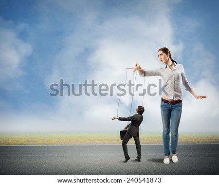 puppeteer controls a businessman holding his strings, the concept of control of business - stock photo
