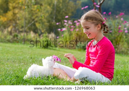 Puppy, kid - lovely girl playing with cute puppy in the garden - stock photo