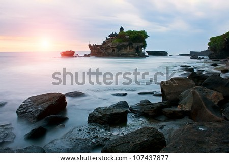 Pura Tanah Lot is one of the most popular and recognizable tourist sights of Bali. This Temple and the area is famous for its dramatic sunsets. - stock photo