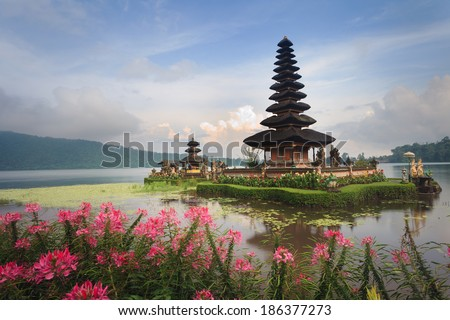 Pura Ulun Danu temple with pink flowers on a lake Bratan, Bali, Indonesia - stock photo