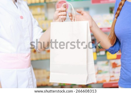 Purchase in a pharmacy. Cropped shot of a paper bag copyspace holding a hand of a customer and a pharmacist  - stock photo