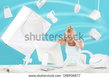 Purchasing power vertigo - on-line shopping . A woman sits in front of a computer monitor and fly above it everyday appliances  - stock photo