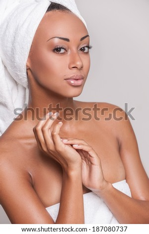 Pure beauty. Beautiful young Afro-American shirtless woman keeping her hands clasped and looking at camera while Isolated on gray background - stock photo