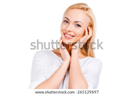 Pure beauty. Beautiful young blond hair woman holding hands on her cheeks and looking at camera while standing against white background - stock photo