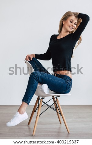 Pure enjoyment. Beautiful young woman posing and keeping eyes closed with smile while sitting on chair against white background - stock photo