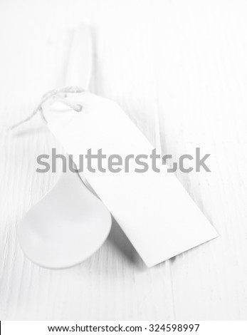 Pure fresh all white cooking concept with a white kitchen spoon tied with a blank gift tag with copyspace on a rustic white wooden table, close up high angle view - stock photo