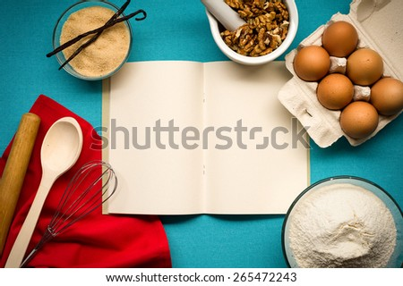 Pure notebook for recording menu, recipe on blue tablecloth with red napkin, kitchen utensils and flour, vanilla, sugar, eggs, walnuts. Close- up view from top. - stock photo
