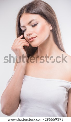 Pure sensuality. Beautiful young woman  standing against white background, looking away. - stock photo