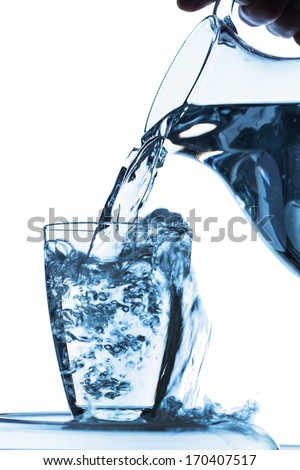 pure water is emptied into a glass of water from a pitcher. fresh drinking water - stock photo