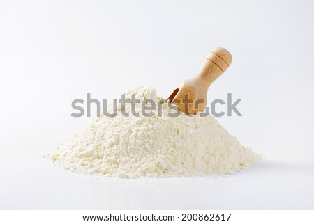 pure wheat flour with immersed measuring spoon - stock photo