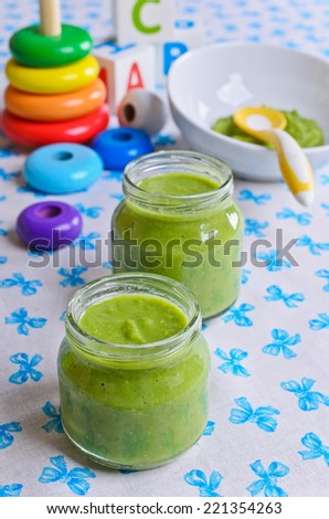 Puree of green in a small glass jar stands amid toys  - stock photo