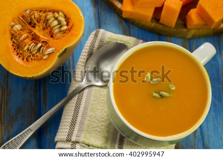 Puree soup with pumpkin, some raw pumpkin, pumpkin slices, spoon, blue background, a table. - stock photo