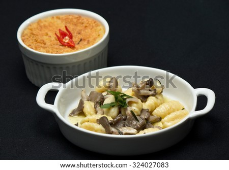 Puree with dried meat with manioc cream and Mini Gnocchi with mushrooms and herbs in butter - stock photo
