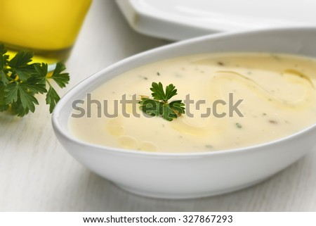 Pureed vegetables with parsley and olive oil on white wooden table - stock photo