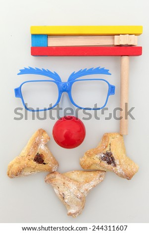 Purim arrangement with Hamantashen, Gragger, Funny glasses and a red nose - stock photo