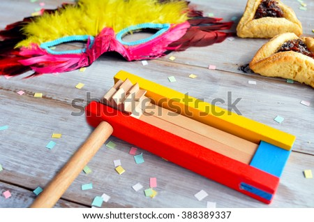 Purim Jewish holiday food and objects: hamantaschen, wooden Purim gragger and carnival mask on a wooden table. - stock photo