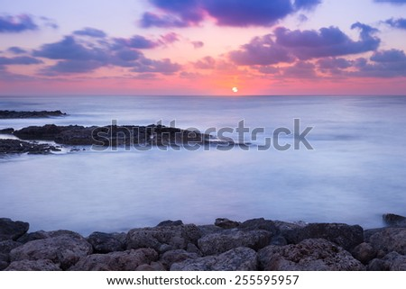 Purple and pink sunset over ocean shore - stock photo