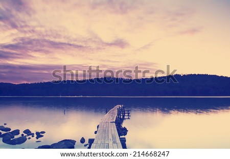 Purple and pink sunset over water and jetty - stock photo