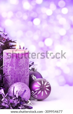Purple and silver Christmas baubles and a candle in front of defocused purple and white lights. - stock photo