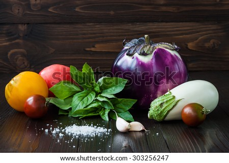 Purple and white eggplant (aubergine) with basil, garlic and tomatoes on dark wooden table. Fresh raw farm vegetables - harvest from the garden in rustic kitchen. Rural still life - stock photo