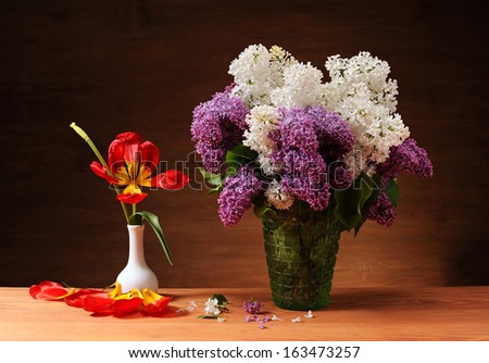 Purple and white lilacs in a vase on the table - stock photo