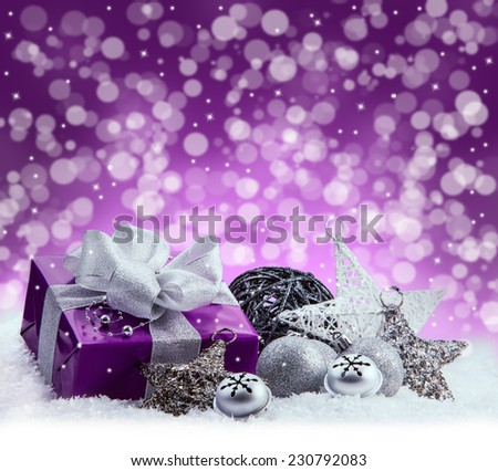 Purple Christmas package , gift of a silver ribbon. Jingle bells , silver christmas balls and christmas stars put on snow. Abstract multicolored blurred background space. - stock photo