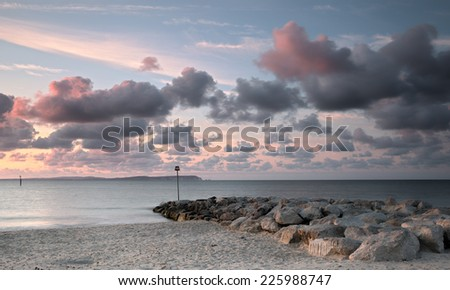 Purple cloudy sunrise at the seashore, with a sea defence groyne, silky smooth sea. Hengistbury Head, Hampshire, UK. - stock photo
