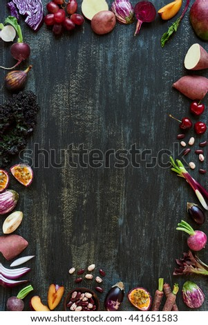 Purple colored fruit and vegetables fresh produce on dark distressed background, plenty of copy space design element for poster, book covers, recipes, website - stock photo