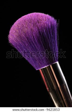 purple cosmetic brush on the black background - stock photo