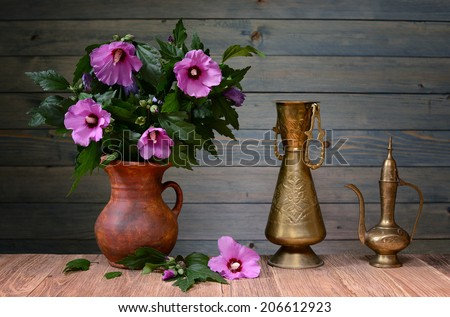 Purple hibiscus in a ceramic vase on the table - stock photo