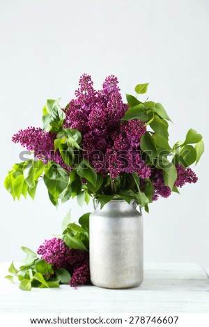Purple lilac flowers in watering can on white wooden background - stock photo