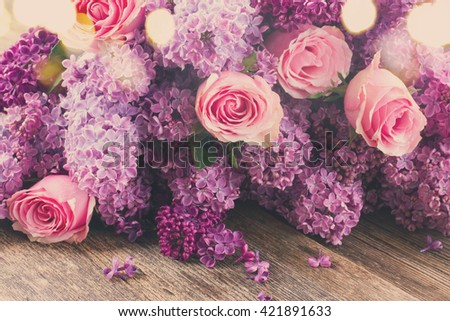 Purple Lilac flowers with pink roses on wooden table , retro toned - stock photo