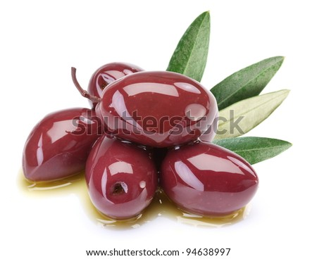 Purple olives in oil with leaves on a white background. - stock photo