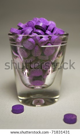 Purple Pills in Shot Glass - stock photo
