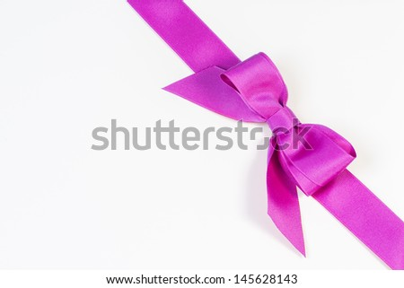 Purple pink ribbon and bow wrapped diagonally across a white background - stock photo