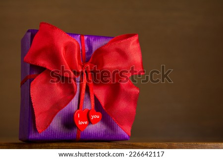 Purple present with red bow an two hearts on ribbon on wooden background, text, I love you, copy space - stock photo