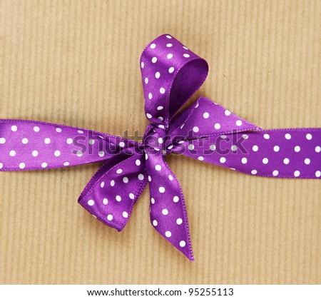 Purple ribbon on a present - stock photo