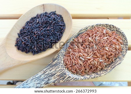 purple rice and red rice in wooden spoon - stock photo