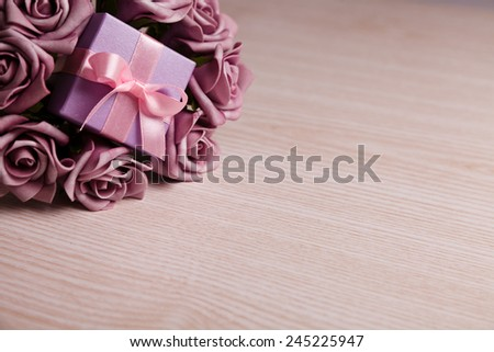 purple roses and gift box with pink ribbon on wooden surface with space for text - stock photo
